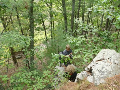Harvey and Elijah on rocks above a steep hillside