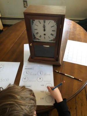 Elijah in front of a clock doing a worksheet
