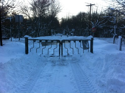 a closed gate blocking the plowed portion of the bike path
