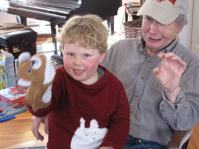 Harvey on Grandpa's lap with a puppet