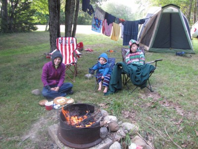 Mama, Harvey, and Lijah in warm pjs and sweatshirts in front of the tent