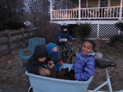 Nisia, Zion, and Lijah bundled up in the blue bike; Harvey on his bike with light
