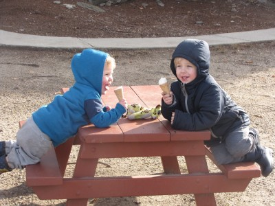 Zion and Lijah, hooded, eating ice cream cones at a little picnic table