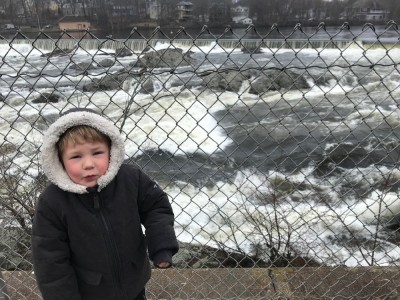 Lijah in snow coat alongside the wild waters of the Merrimack River