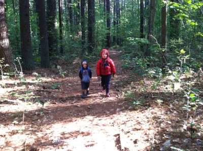 Zion and Harvey walking in the woods; Harvey with winter jacket
