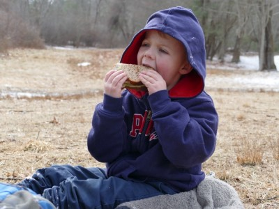 Zion biting into a sandwich picnicking in a field