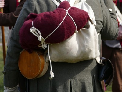 a backpack, bedroll, and canteen on the back of a reenactor
