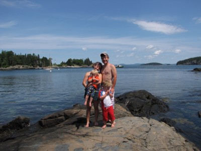 the Archibalds posing on a rock in the waters of Compass Harbor
