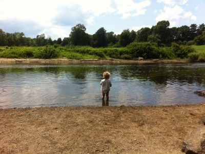 Harvey standing in the Concord River with no pants on
