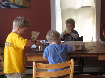 Harvey, Zion, and Lijah working on cooking (and eating) at the kitchen table