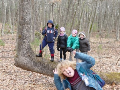 Zion and Lijah posing with friends on a horizontal tree trunk, Harvey photobombing