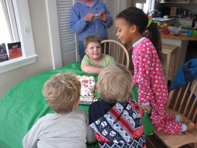 the boys and Nisia getting ready to share a gingerbread house