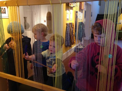 kids experimenting with weaving at a museum