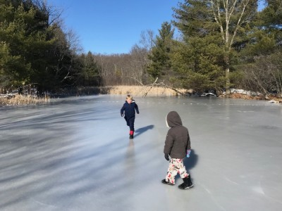 Zion running to slide on the cranberry bog ice, Lijah watching