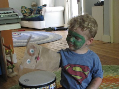 Lijah in green facepaint playing with a paper-bag puppet