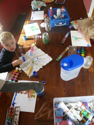 colorful paints on the kitchen table as the boys work