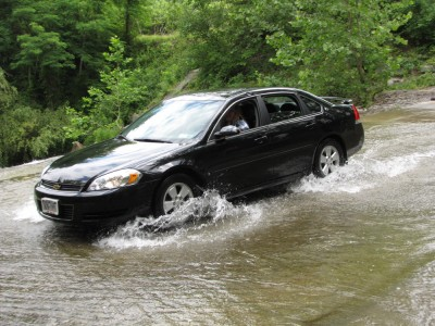 a car driving through the creek at the ford
