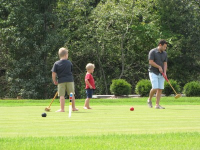 the boys and Uncle Jake playing croquet on a manicured lawn