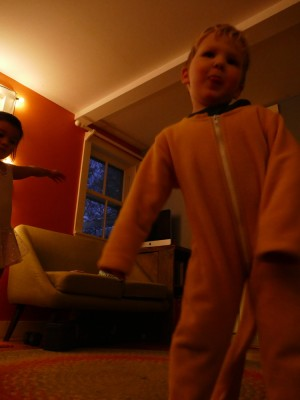 Lijah and Kamilah dancing in the low-light playroom