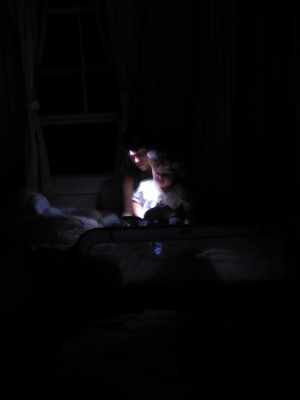 Mama and Harvey reading by the light of the headlamp