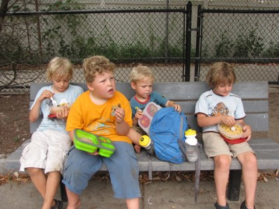 Harvey, Zion, Ollie, and Eliot on a bench having lunch