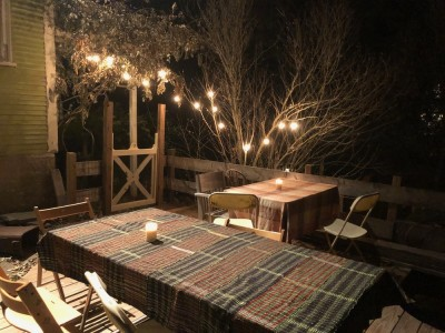 tables set with tablecloths and candles under the lights on our back deck