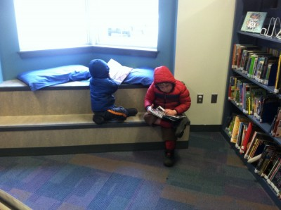 Harvey and Zion reading books in the library in their winter coats