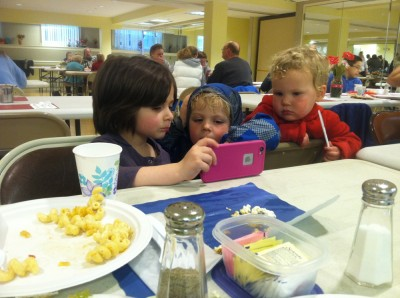 Zion and Lijah watching a show on a friend's phone at the community dinner
