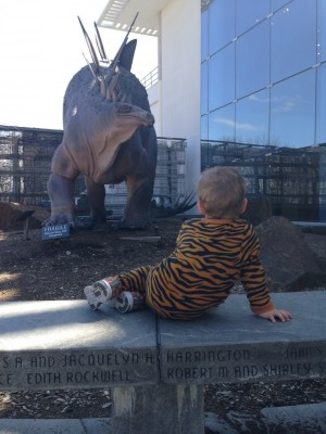 Lijah in tiger pajamas lounging on a wall in front of a statue dinosoar