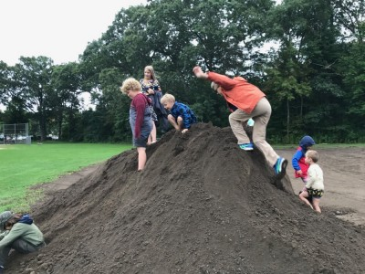 kids playing on a big dirt pile