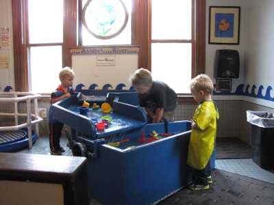 the boys playing in the water table at the childrens museum