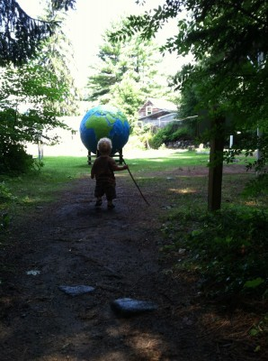 Lijah carrying a walking stick approaching a giant globe