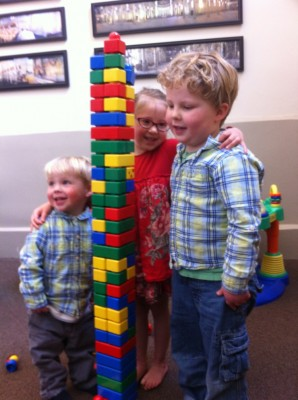 Zion, Taya, and Harvey posing by a tall tower of toddler Lego blocks