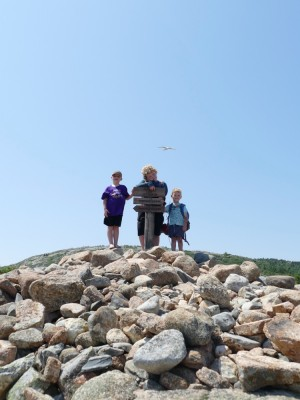 the boys posing atop Dorr Mountain in Acadia National Park