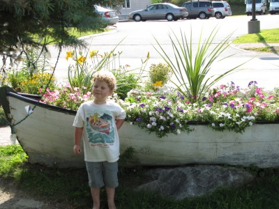 Harvey, in his Burt Dow shirt, posing by a dory planted with flowers
