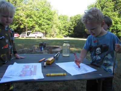 Lijah and Henry working on coloring pages by the remains of the fire