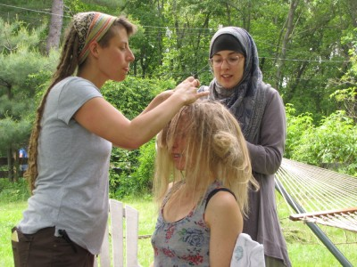 Leah and Kelsey dreading Mary's hair in the backyard