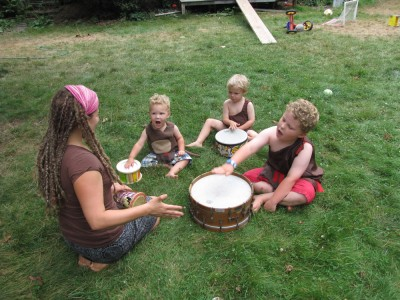 Mama leading the boys in a drum circle on the lawn