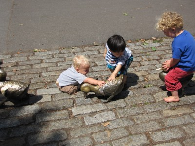 Harvey, Zion, and Timothy playing with the duckling statues