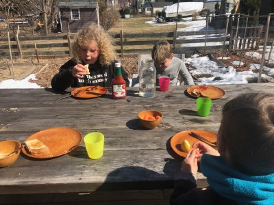 the boys eating lunch at the picnic table with snow in the background