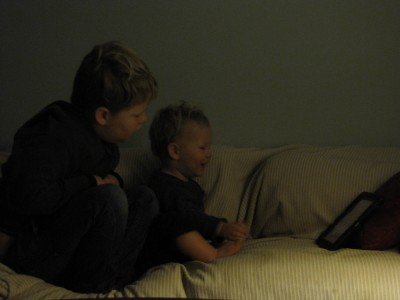 Harvey and Lijah on the couch in the dark, looking at the iPad
