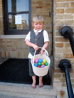 suited and barefoot Zion on the steps with a basket full of eggs