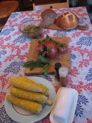 corn, tomatoes, basil, pesto spaghetti, and bread on the table