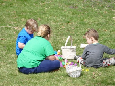 the boys sitting on the lawn opening their easter eggs