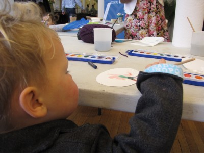 Lijah reaching up high to paint a paper egg on a table