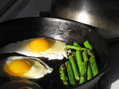 fried eggs and asparagus in the skillet