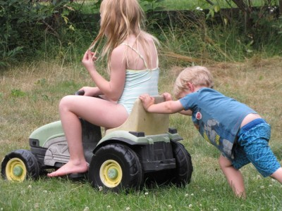 Zion pushing Megan on the pedal tractor