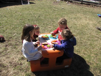Harvey, Zion, and friends sitting at the little plastic picnic table outside