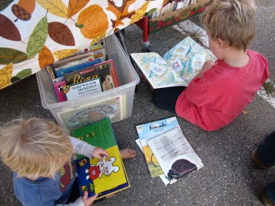 Zion and Harvey sitting on the pavement in the book sale booth looking at books