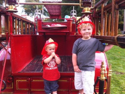 Harvey and Zion on the back of a 1911 fire truck
